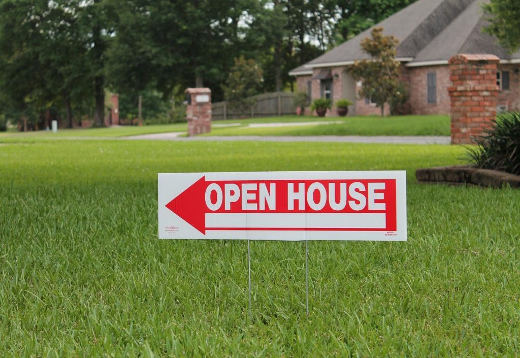 Open House sign with red arrow and white letters.  Has large yard with green grass